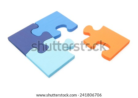Stand out from the crowd - orange jigsaw puzzle piece going into a blue puzzle - stock photo