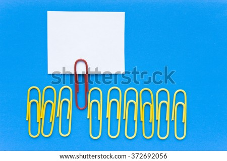Stand out, think different, uniqueness concept - red paperclip standing out from a crowd of yellow paperclips with a blank paper card for your text