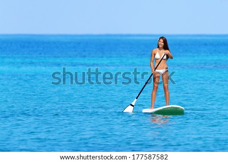 Stand up paddle board woman paddleboarding on Hawaii standing happy on paddleboard on blue water. Young mixed race Asian Caucasian female model on Hawaiian beach on summer holidays vacation travel. - stock photo