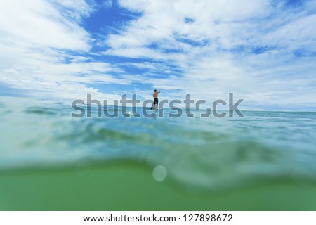 Stand up paddle boarder on open ocean - stock photo