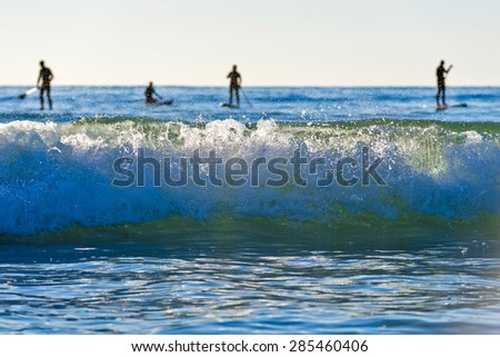 Stand up paddle boarding in Pacific surf - stock photo