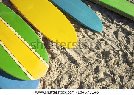 Stand up paddle long board surfboards in Brazil colors on bright morning in Copacabana Beach Rio de Janeiro - stock photo