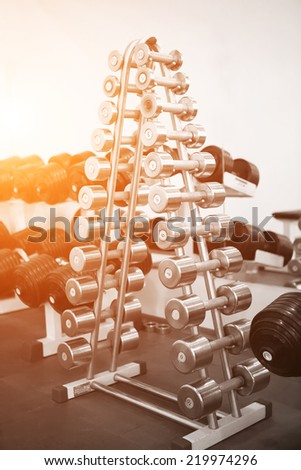 stand with dumbbells of different weights in a luxury gym - stock photo