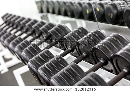 Stand with dumbbells. Sports and fitness room. Weight Training Equipment - stock photo