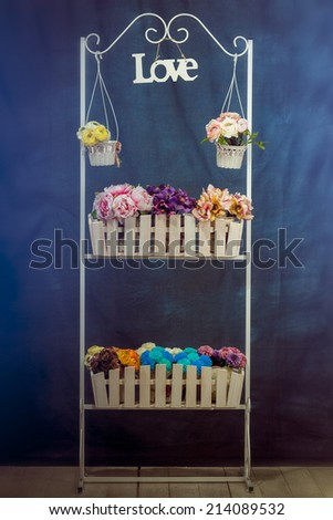 stand with flowers, flowers on the table wooden desk with artificial flowers, fence - stock photo