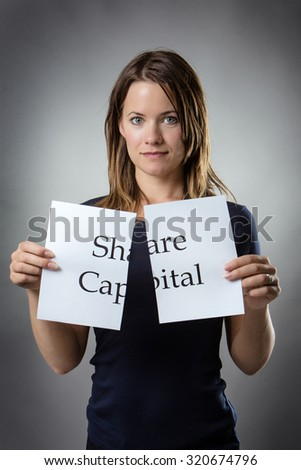 stand woman cutting paper in half with the word share capital written on the paper