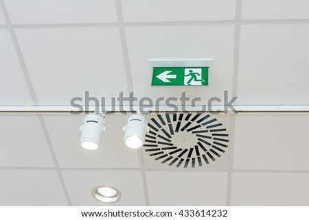 Standard international symbol safe exit sign is hanging from the ceiling of the modern office ceiling with air duct and lamps. - stock photo