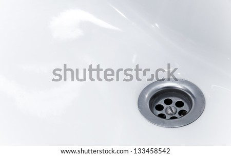 Standard round drain hole in white domestic sink - stock photo