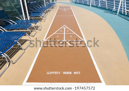 Standard Shuffleboard court with blue lounge chairs - stock photo