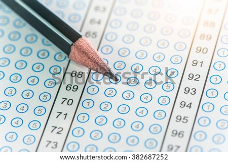 Standardized test form with bubbled in and a black pencil, focus on answer sheet - stock photo
