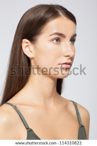 Standart model tests of young pretty girl over gray background - stock photo