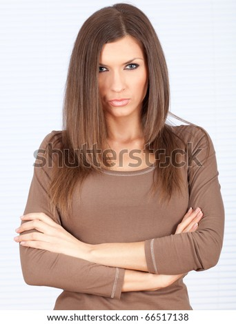 standing angry beautiful woman with crossed arms - stock photo