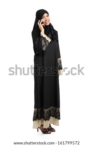 Standing arab woman talking on the phone isolated on a white background       - stock photo