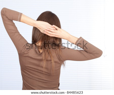 standing back stretching young woman in brown blouse - stock photo