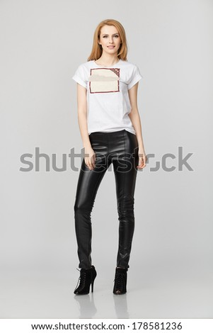 standing beautiful young lady with leather pants  - stock photo
