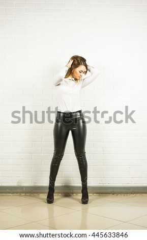 standing beautiful young lady with leather pants