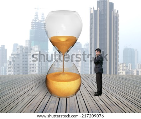 standing businessman looking hourglass with city skyscraper and wooden floor - stock photo