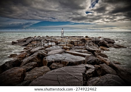 standing businessman on sea rock - stock photo