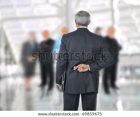 Standing Businessman with fingers crossed behind back. He is standing in front of an out of focus group of people. Horizontal format.