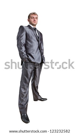 Standing confident businessman with hands in pockets. Isolated on white