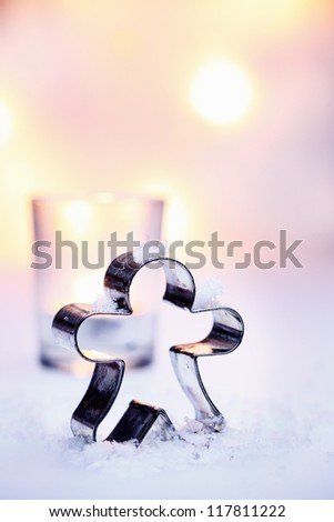 Standing figure cookie cutter Christmas background in snow against a backdrop of soft glowing party lights with copyspace for your seasonal greeting - stock photo