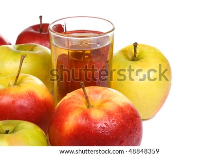 standing glass full of juice and apples
