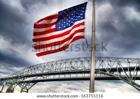 Standing Guard.  Old glory stands guard over an international border crossing. The background contains the Blue Water Bridges, which are the second busiest border U.S. and Canadian border crossing.  - stock photo