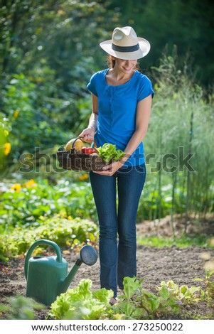 Standing in her garden, portrait of a beautiful woman holding a fresh vegetables basket outdoor - stock photo