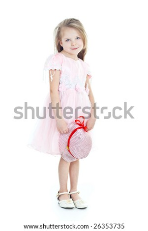 Standing little blonde girl in pink dress with hat in hands