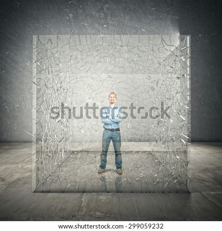 standing man inside broken glass cube - stock photo