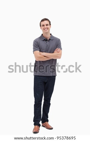 Standing man smiling while crossing his arms and against white background - stock photo