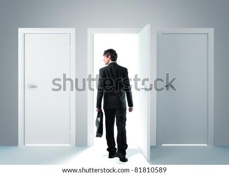 standing man walking toward open door - stock photo