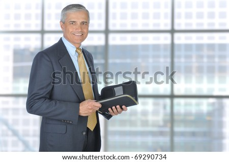 Standing Middle Aged Businessman with Planner Notebook in Modern Office Setting, Horizontal Format. - stock photo