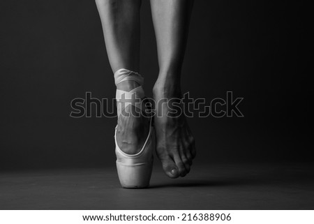 Standing on tip toe, monochrome - stock photo