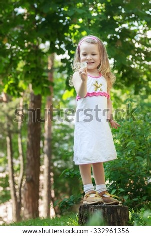 Standing on tree stump smiling toddler girl with white Taraxacum officinale in arm - stock photo