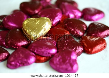 Standing out : A gold heartshaped  in amongst red and magenta foil covered chocolates