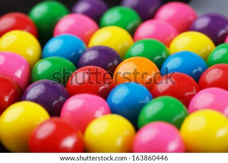 Standing out concept: focus on the only orange gumball amongst the colorful bubble gums - stock photo