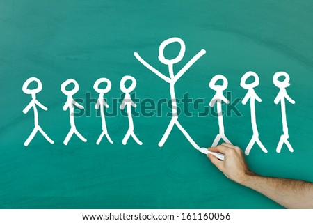 Standing out from crowd concept on green blackboard - stock photo