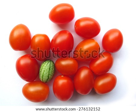 Standing out from the crowd, one green cucamelon sits among red cherry tomatoes - stock photo
