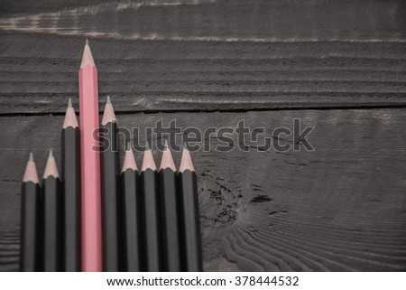 Standing out from the crowd.Pink pencil stands out from the crowd of other black pencils on a wood background.Concept of business success.Strategy,uniqueness,independent,dissent,think differently - stock photo