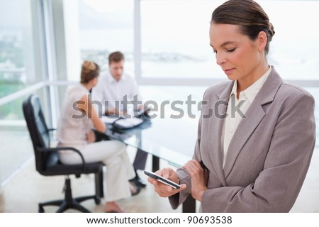 Standing real estate agent with cellphone and sitting clients behind her - stock photo