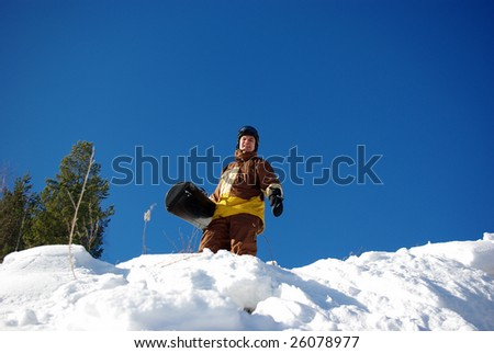 Standing snowboarder on slope - stock photo