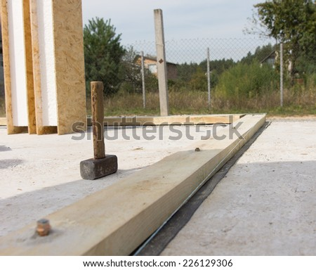 Standing Vintage Mallet Tool of a Carpenter at the Real Estate Construction Site with Pre-installed Strong Wooden Building Foundation. - stock photo