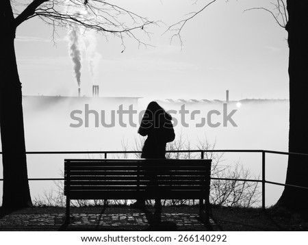 standing woman depressed and alone in front of a park bench in the fog - stock photo