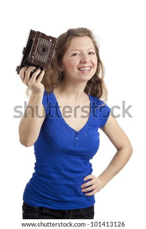Standing woman holding up old camera - stock photo