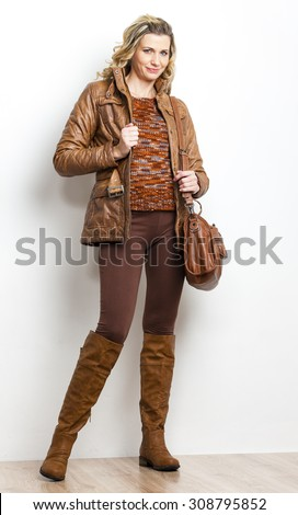 standing woman wearing brown clothes and boots with a handbag - stock photo