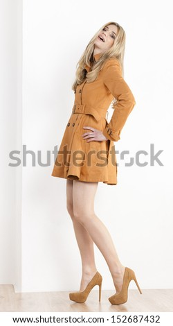 standing woman wearing brown coat and pumps