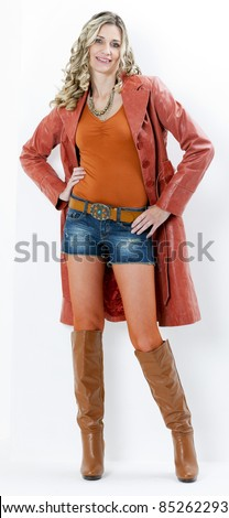 standing woman wearing fashionable brown boots and coat