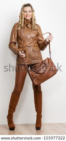 standing woman wearing fashionable brown clothes and boots with a handbag