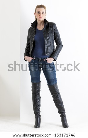 standing woman wearing jeans and black boots - stock photo